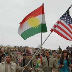 Local citizens wave Kurdish and American flags during the Kurdish regional government new year's celebration in Dahuk. The celebration was witnessed by Maj. Gen. Mark P. Hertling, the 1st Armored Division and Task Force Iron commander and other military leaders.